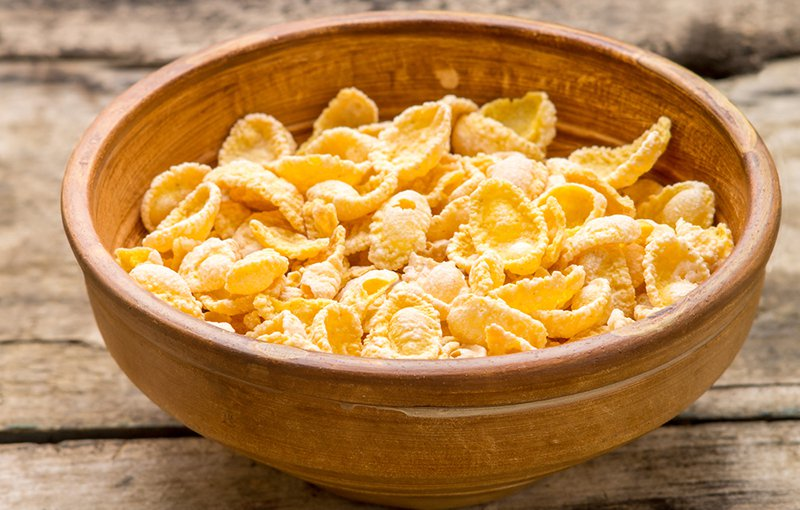Clay bowl with dried corn flakes on wooden table. Healthy eating background