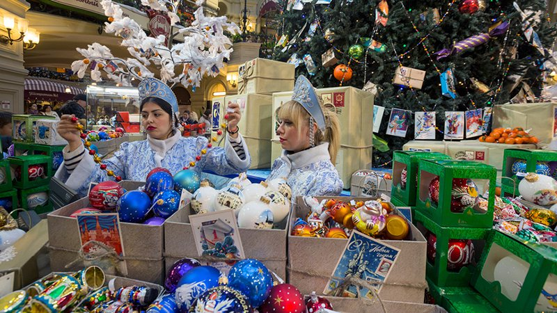 Продажа ёлочных игрушек и украшенная новогодняя елка в Главном универсальном магазине (ГУМ) города Москвы, Россия