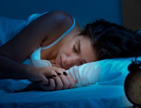 Woman sleeping in a bed in a dark bedroom