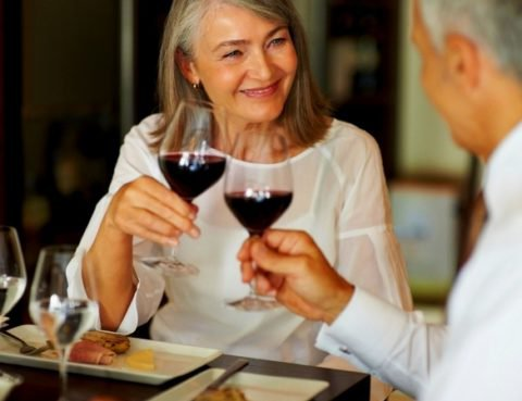 Portrait of elderly woman toasting wine with her husband at restaurant