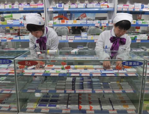 epa02657923 Chinese pharmacy staff members change price tags to show the reduction in prices of certain medicine in Shenyang, Liaoning Province of China, 28 March 2011.  China cut the maximum retail price for more than 1,200 types of antibiotics and circulatory system drugs on 28 March in a move aimed at battling inflation and warding off resentment over high healthcare costs.  EPA/MARK